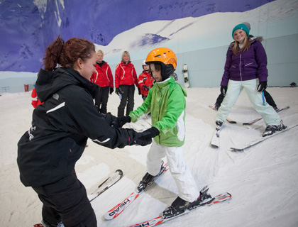 Chill FactorE- Trainer teaching child to ski